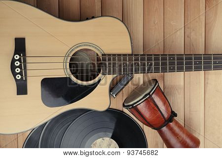 Guitar with vinyl records and African drum on wooden table close up