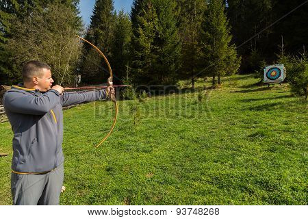 A man shoots a bow. Man engaged in archery. poster