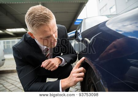Man Looking For Scratches On His Car
