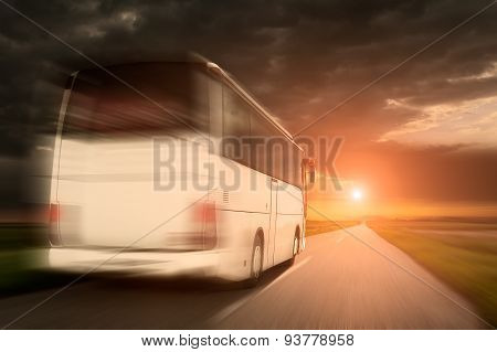 White Bus In Speed Driving On An Empty Asphalt Road