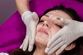 Beauty treatments in the beauty salon. Beautician revitalizing facial. Facial massage. Beauty, facial, beautician. poster