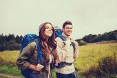 adventure, travel, tourism, hike and people concept - smiling couple walking with backpacks outdoors poster
