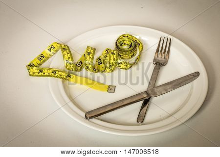 White Plate With  Bun,  Yellow Tape Measure And Cutlery On  Background