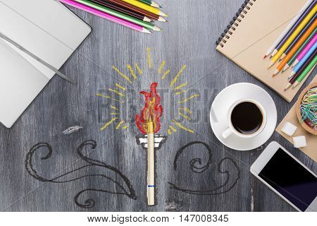 Creative torch fire sketch around pen on wooden desktop with other colorful supplies smartphone and coffee cup