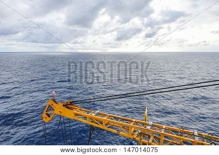 Crane boom structure and metal sling on blue sky and sea background