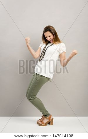Beautiful young happy woman with arms up