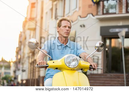 Mature man on yellow scooter. Thoughtful guy on street background. Tourist is perplexed. Can't remember the address.