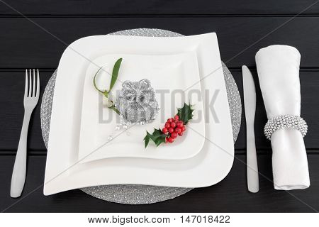 Christmas dinner table setting with white china plates, cutlery, linen serviette and ring, holly, mistletoe and silver gift box bauble decoration with bead strand over dark wood background.