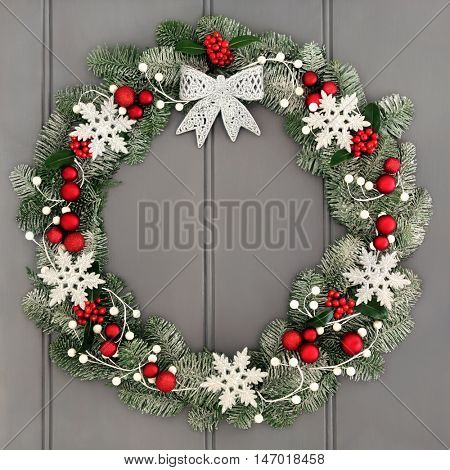 Christmas wreath decoration with silver bow, red bauble and white snowflake decorations, holly and snow covered blue spruce fir over grey front door background.
