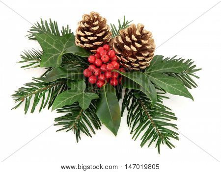 Winter and christmas floral arrangement of holly with red berries, ivy, gold pine cones and  fir over white background.