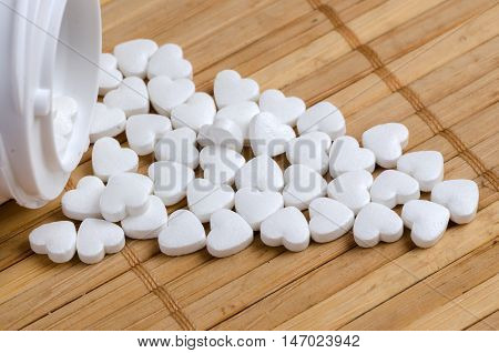 White pills in the form of heart close up