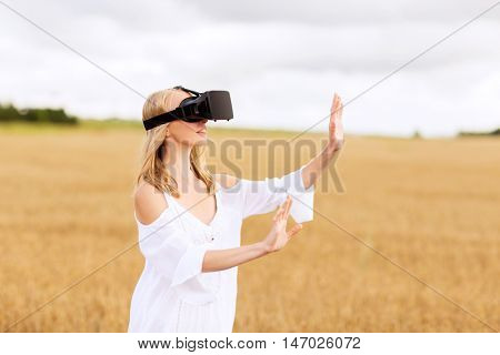 augmented reality, gaming, summer holidays, technology and people concept - happy young woman with virtual reality headset or 3d glasses on cereal field touching something