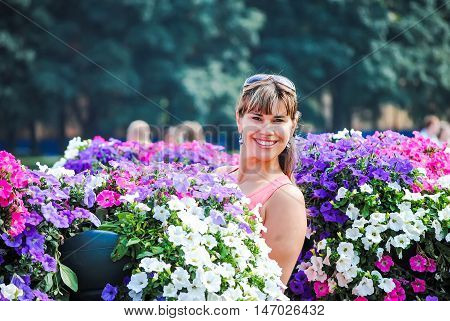 smiling girl looking out of flower beds