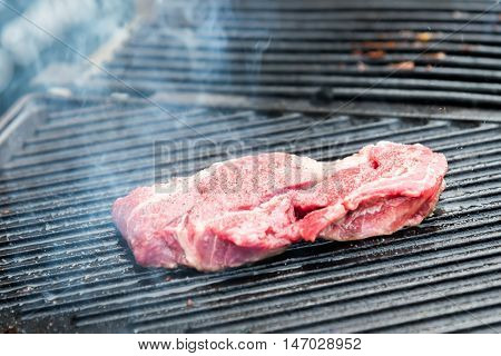 Raw Steak With Spices On Metal Grill