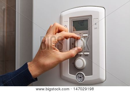 Men hand regulate low temperature on 40 degree in control panel of central heating.