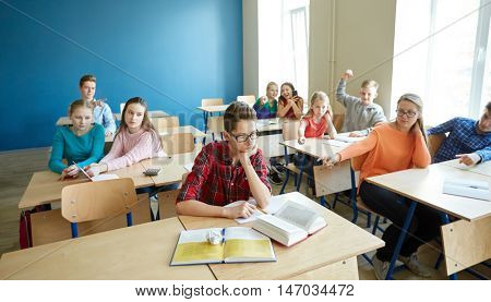education, bullying, conflict, social relations and people concept - student boy in glasses reading book and suffering of classmates mockery at school