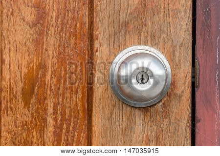 Close up of doorknob with wooden door