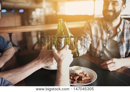people, men, leisure, friendship and celebration concept - happy male friends drinking beer and clinking bottles at bar or pub