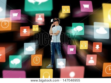 3d technology, augmented reality, gaming, cyberspace and people concept - happy young man in virtual reality headset or 3d glasses thinking with menu icons over black background