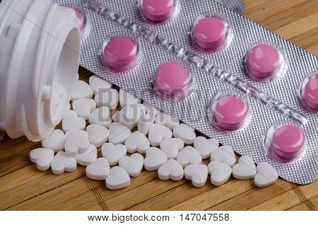 Pink and white pills in the form of heart close up