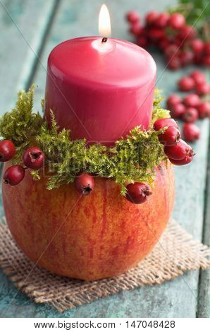 Autumnal decoration with fruity candleholder on wood