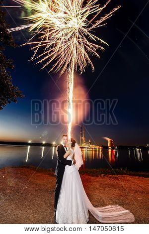 Newlyweds Kissing Near Lake By Night - Fireworks