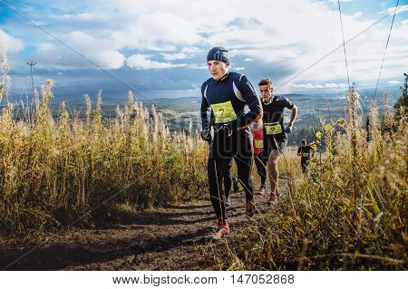 Revda Russia - September 10 2016: group of men runners marathon running up mountain on blue sky background during marathon Vertical kilometer