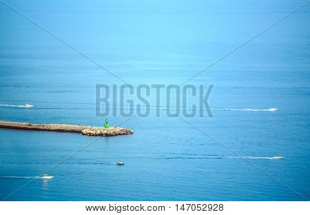Minimalistic seascape of blurred speedboat and jetty with small lighthouse