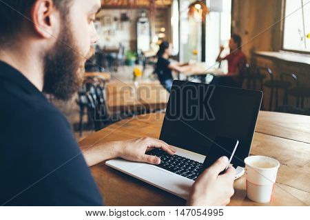 Cropped shot of a man using laptop and surfing the web, browsing social network pages. Holding cell phone in hand and downloading the new app. Blank copy space screen for your text and content