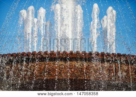 Many water fountain jets over blue sky, close-up