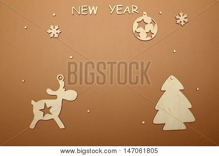 Christmas background with the text of the new year, wooden silhouettes of trees, reindeer and Christmas tree ball
