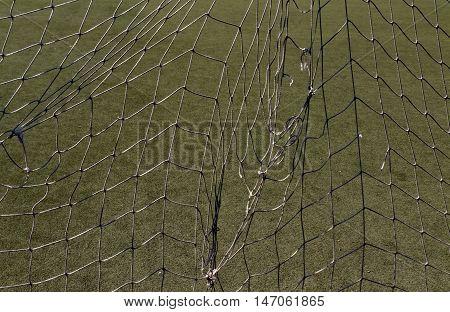 Old Torn Football Net Against Green Loan.