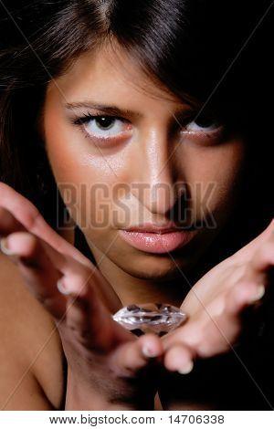 Beautiful girl holding a big diamond in her hand