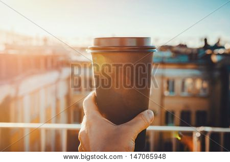 hands holding hot craft cup of coffee or tea in morning sunlight with view to blurred city background. Enjoy lifestyle take away breakfast concept. woman on the roof with hot drink
