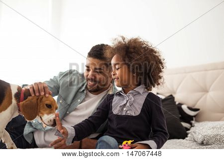 African american family playing with a dog.
