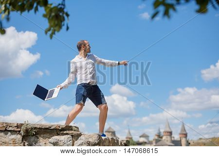 young man throws a laptop against blue sky