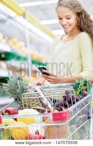 Portrait of a Smiling Woman Pushing a Shopping Cart and Using Smartphone in a Supermarket