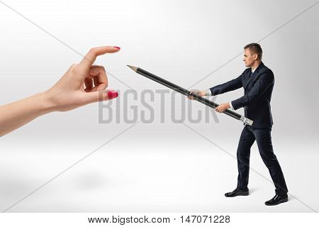 Businessman defending himself from big woman's hand with big pencil in his arms. Boss and subordinate. Standing against domination. Disobedience and insubordination.