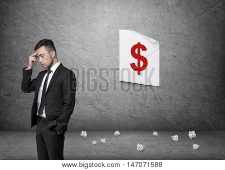 Businessman with his hand on his forehead pondering on the background of a concrete wall with a dollar sign poster and pieces of paper on the floor. Making money. Ideas and inspiration.