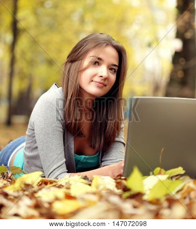 beauty girl with laptop PC in autumn park