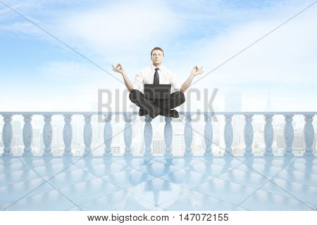 Young businessman with laptop meditating on concrete balcony pillars. City and bright sky background. 3D Rendering