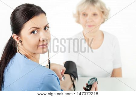 Medical Professional Taking Blood Pressure of a Senior Citizen