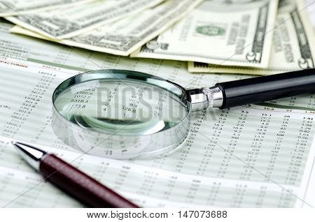 United States paper currency with a magnifying glass and pen on top of financial charts