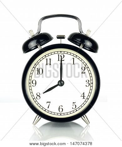Alarm Clock isolated on white in black and white showing eight o'clock.