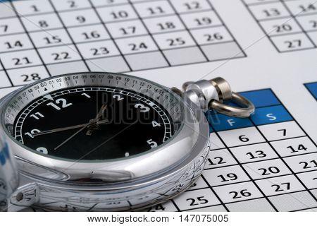 Pocket watch/stop watch on top of a calendar
