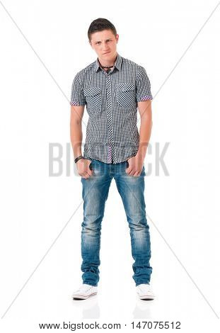Serious suspicious young man standing with hands in pockets, isolated white background. Full length portrait of anger teen boy.