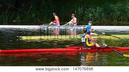 St Neots, Cambridgeshire, England - July 24, 2016: Rowers and colorful boats on the River Ouse at St Neots Cambridgeshire.