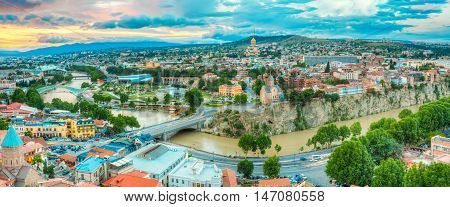 The Panoramic Top View Of  Central Historic Part Of Summer Tbilisi, Georgia With All Famous Landmarks And Winding Kura River Under The Scenic Sunset Sunrise Sky