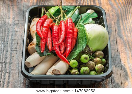 Tom yam ingredients set for Thai cooking in black plactic pallet on wooden table