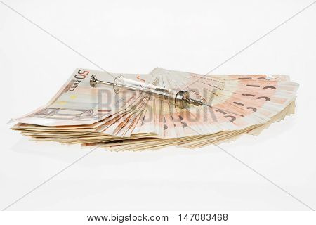 Fan from fifty euros and medical syringe. Many mass currency isolated on white background. Euro cash. Money for the purchase of medicines drugs or narcotic